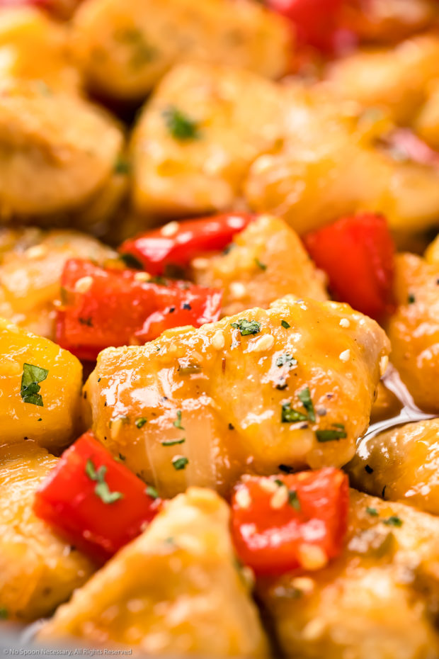 Angled, extreme up-close photo of Apricot Chicken stir-fried with onions, peppers and pineapples and garnished with sesame seeds and chopped cilantro.