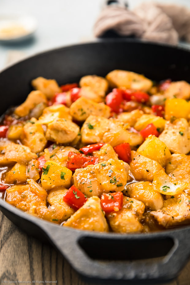 Angled photo of apricot chicken stir-fried with onions, peppers and pineapples and garnished with sesame seeds and chopped cilantro in a cast iron skillet.