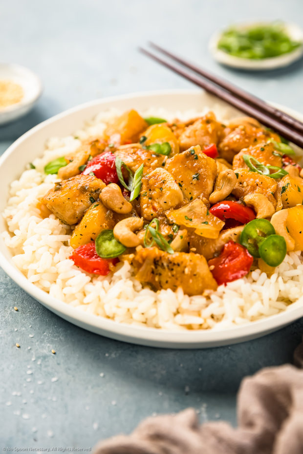 Angled shot of Apricot Chicken stir-fried with onions, peppers and pineapples on a bed of white rice in a white bowl with a pair of wooden chopsticks resting on the side of the bowl; with ramekins of sesame seeds and sliced scallions blurred in the background.