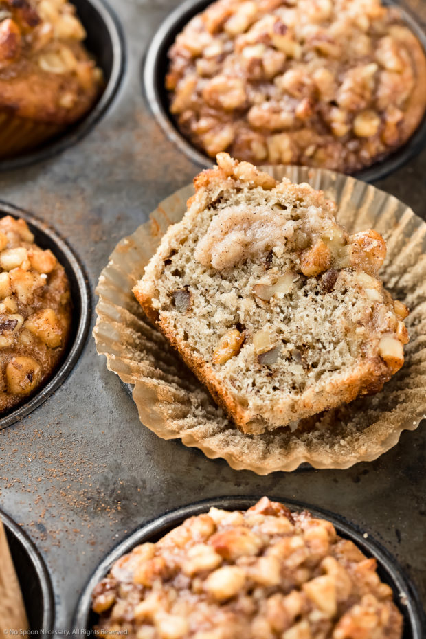 Angle, up-close photo of Banana Nut Muffins in a metal 6 count muffin pan with the focus of the shot on one of the muffins cut in half showcasing the interior of the muffin.