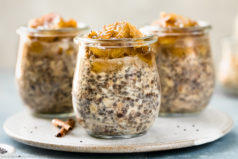 Straight on photo of three individual jars of Banana Overnight Oats on a white plate with spoons next to the jars and a glass jar of rolled oats blurred in the background.