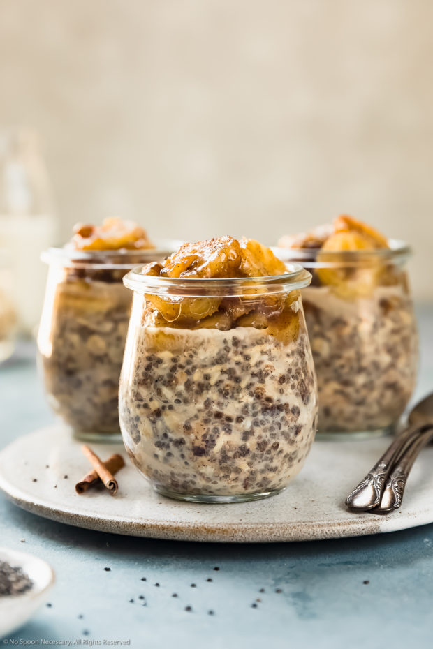 Straight on photo of three individual jars of Banana Overnight Oats on a neutral colored plate with spoons next to the jars and a ramekin of chia seeds in front of the plate.