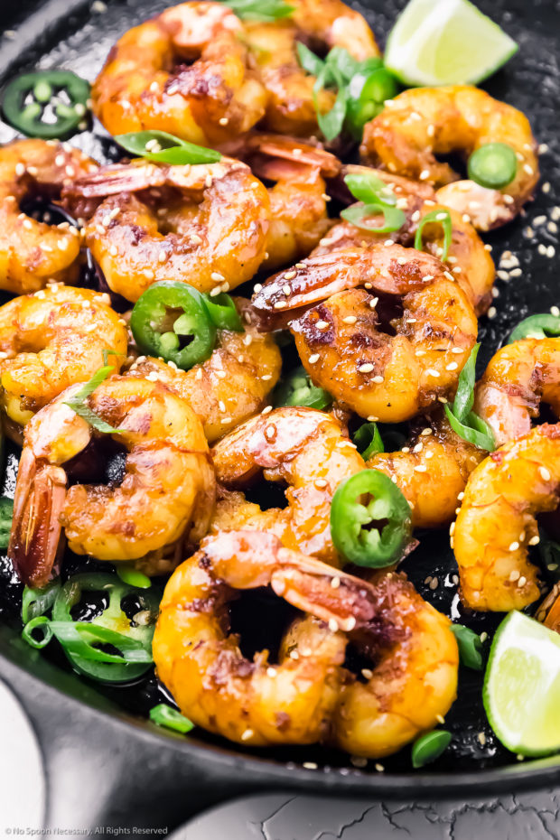Angled, overhead photo of Garlic Honey Shrimp garnished with lime wedges, jalapeno slices, and sliced scallions in a large cast iron skillet