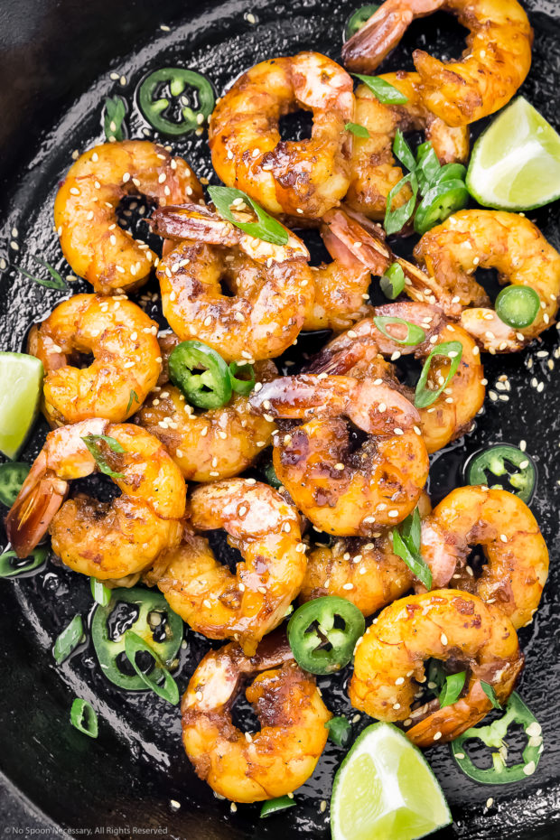 Overhead shot of a cast iron skillet filled with Sticky Honey Garlic Glazed Shrimp, lime wedges, jalapeno slices, and sliced scallions.