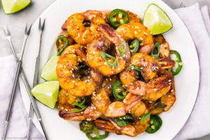 Overhead photo of Honey Garlic Shrimp garnished with scallions and lime wedges on a white plate with more lime wedges next to the plate.