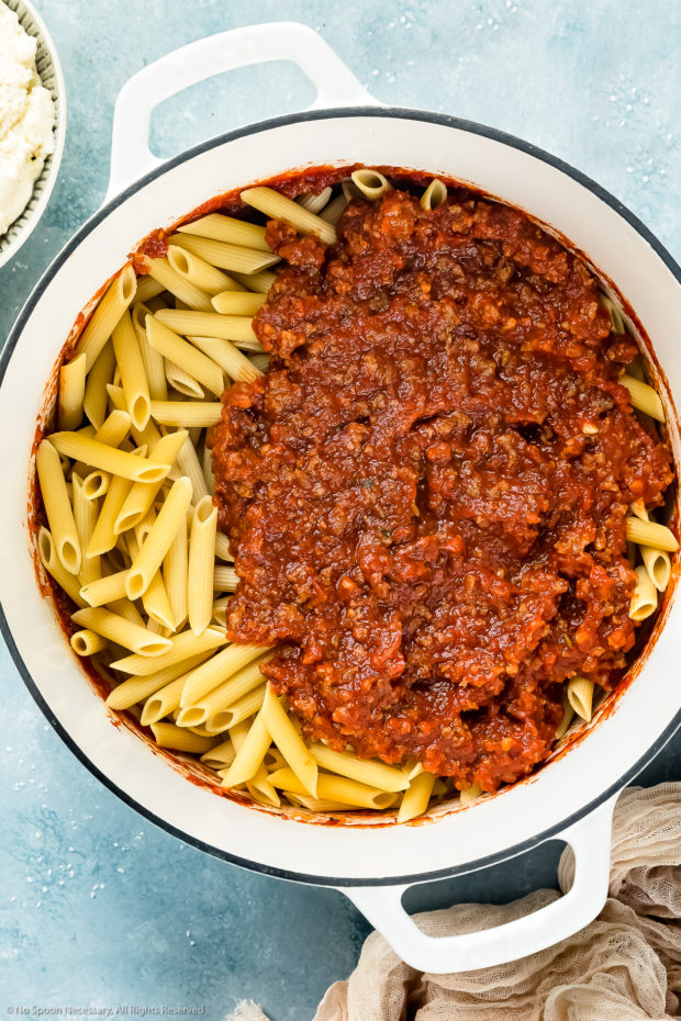 Overhead photo of soaked ziti noodles with sausage tomato sauce in a large white pot with a bowl of ricotta next to the pot - photo of step 8 of the ziti with sausage Recipe.