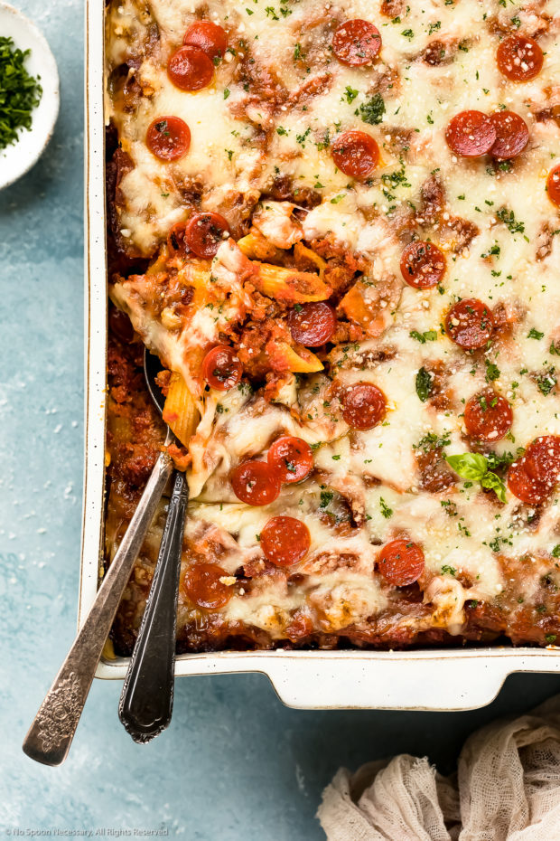 Overhead, up-close photo of baked pasta casserole garnished with fresh basil and mini pepperonis in a white casserole dish with serving spoons tucked into the bottom corner of the ziti exposing ziti noodles and sausage.