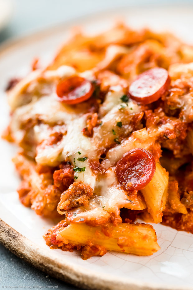 Angled, up-close photo of a serving of Sausage Baked Ziti garnished with chopped parsley and mini pepperonis on a white plate.