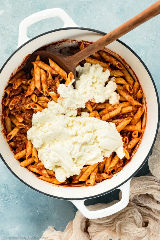 Overhead photo of soaked ziti noodles tossed with sausage tomato sauce and topped with ricotta in a large white pot with a wooden spoon inserted into the pot - photo of step 9 of the recipe.