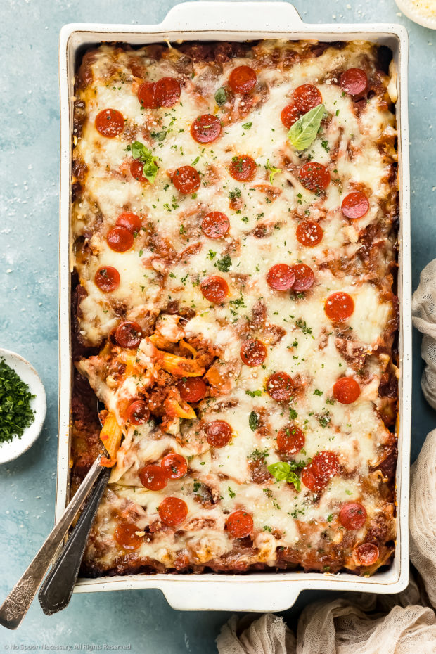 Overhead photo of Sausage Baked Ziti garnished with fresh basil and mini pepperonis in a white casserole dish with serving spoons tucked into the bottom corner of the ziti exposing ziti noodles and sausage; with a tan linen and ramekins of chopped parsley and grated parmesan arranged around the casserole dish.