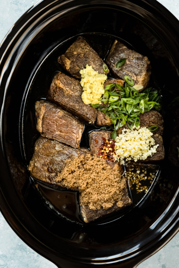 Overhead photo of a black slow cooker insert filled with seared short ribs, brown sugar, garlic, ginger, scallions, red pepper flakes and Korean sauce - photo of step 3 of the recipe.