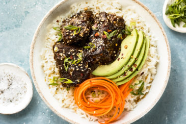Overhead, landscape shot of Slow Cooker Korean Short Ribs on a bed of rice with sliced avocado and carrot ribbons in a white bowl with ramekins of salt and sliced scallions arranged around the bowl.