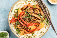 Overhead, landscape shot of Slow Cooker Sweet Chili Chicken on a bed of lo mein noodles in a neutral colored bowl with a pair of wooden chopsticks resting on the side of the bowl and ramekins of sesame seeds and sliced scallions arranged around the bowl.