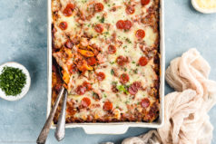 Overhead, landscape photo of Sausage Baked Ziti garnished with fresh basil and mini pepperonis in a white casserole dish with serving spoons tucked into the bottom corner of the ziti exposing ziti noodles and sausage; with a tan linen and ramekins of chopped parsley and grated parmesan arranged around the casserole dish.