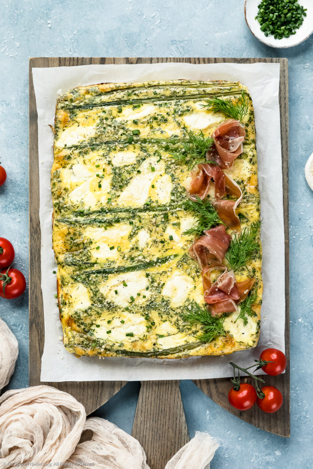 Overhead photo of Asparagus Baked Frittata topped with prosciutto on a parchment paper lined wood serving board with a tan linen, cherry tomatoes and ramekin of snipped chives arranged around the board.