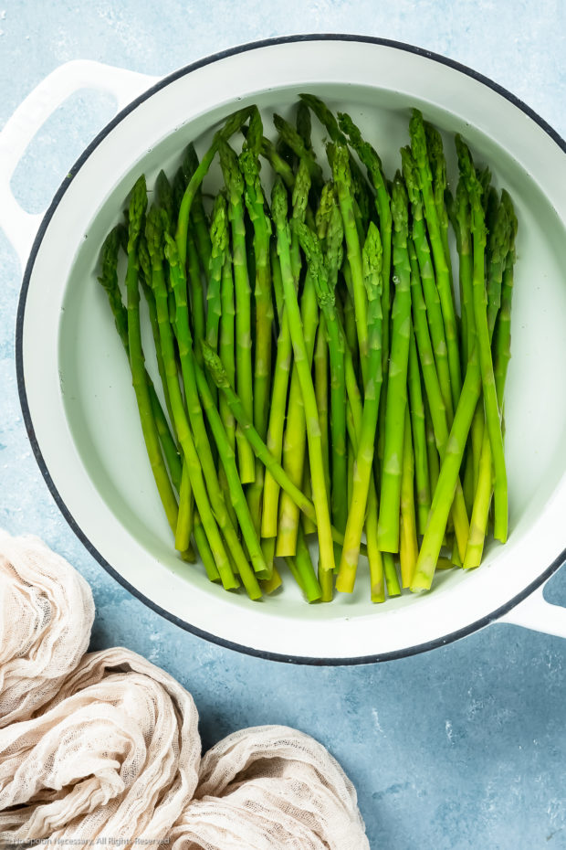 Overhead photo of blanched asparagus in a large white pot filled with ice cold water - photo of step 1 and 2 of the asparagus mimosa recipe.