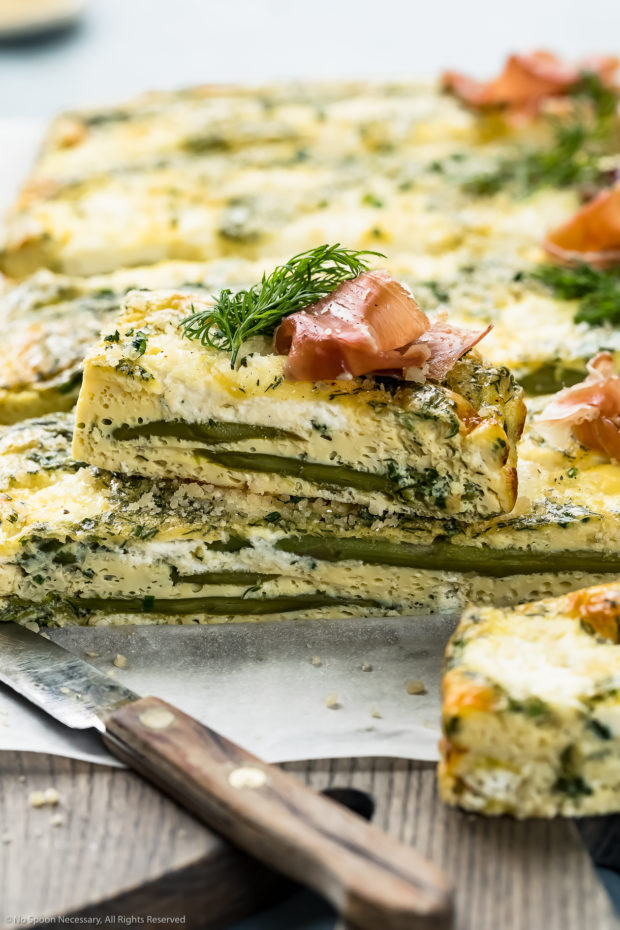 Straight on photo of Asparagus Baked Frittata sliced into long pieces with one pieces arranged on top of another to showcase the inside of the frittata