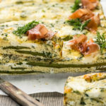 Straight on, landscape photo of Asparagus Baked Frittata sliced into long pieces with one pieces arranged on top of another to showcase the inside of the frittata