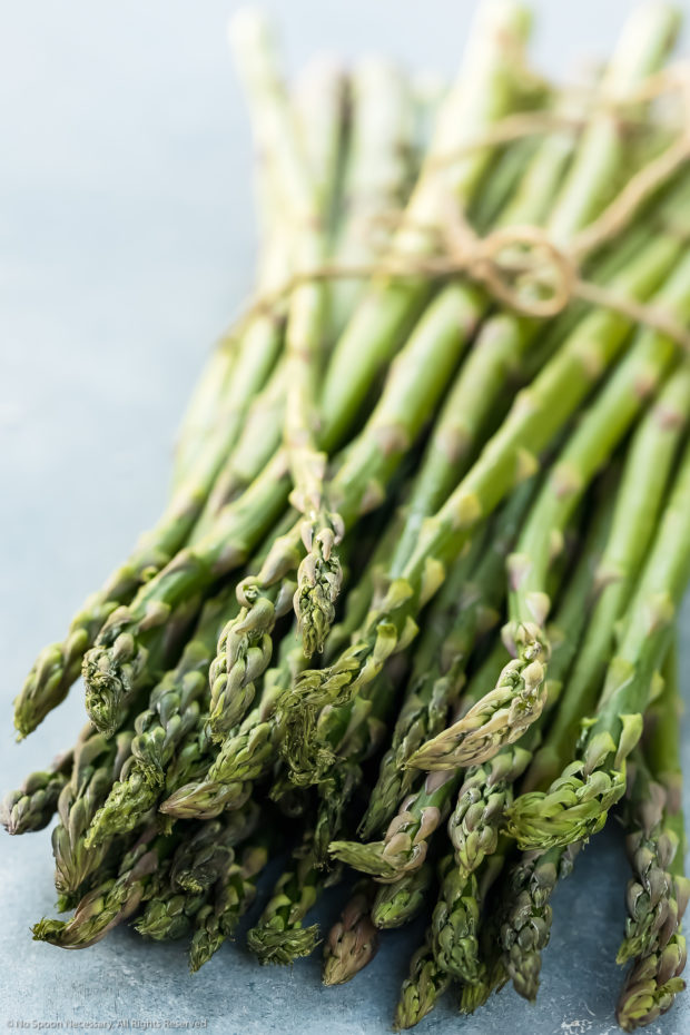 Angled photo of a fresh asparagus bundle wrapped with twine - photo of the main ingredient in the asparagus mimosa recipe.