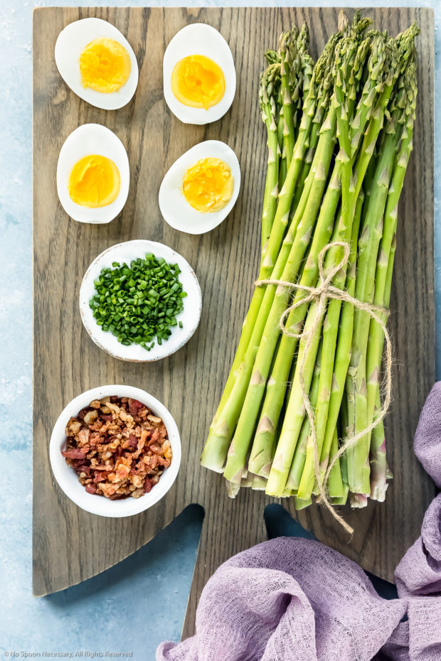 Overhead photo of all the ingredients needed to make asparagus mimosa (hard boiled eggs, chives, crumbled bacon and asparagus) on a gray wood board with a purple linen off to the side.