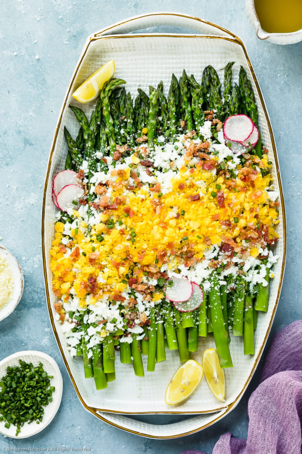 Overhead photo of Asparagus Mimosa garnished with crumbled bacon, grated parmesan and slices of radishes on a large white platter with a mini pouring jug of vinaigrette and ramekins of grated cheese and snipped chives arranged around the platter.