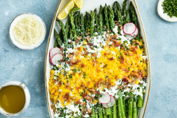Overhead, landscape photo of Asparagus Mimosa garnished with crumbled bacon, grated parmesan and slices of radishes on a large white platter with a mini pouring jug of vinaigrette and ramekins of grated cheese and snipped chives arranged around the platter.
