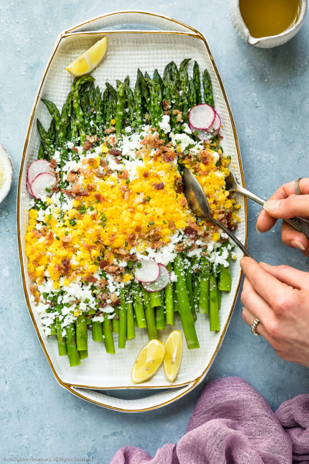 Overhead photo of Asparagus Mimosa garnished with crumbled bacon, grated parmesan and slices of radishes on a large white platter with two hands holding serving utensils tucked under the asparagus to serve it.