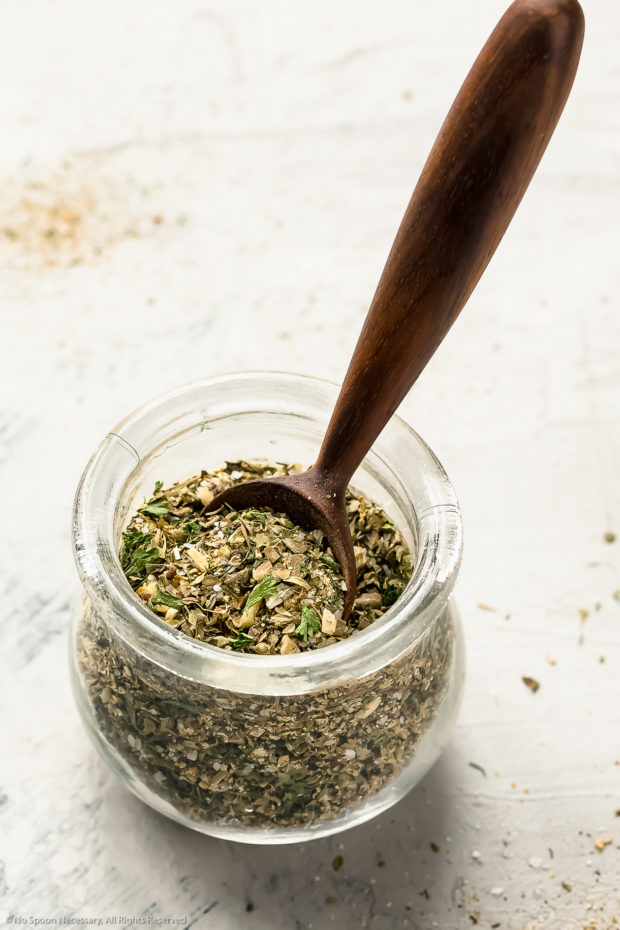 Angled shot of a glass jar filled with homemade greek spices with a small wooden teaspoon inserted into the jar.