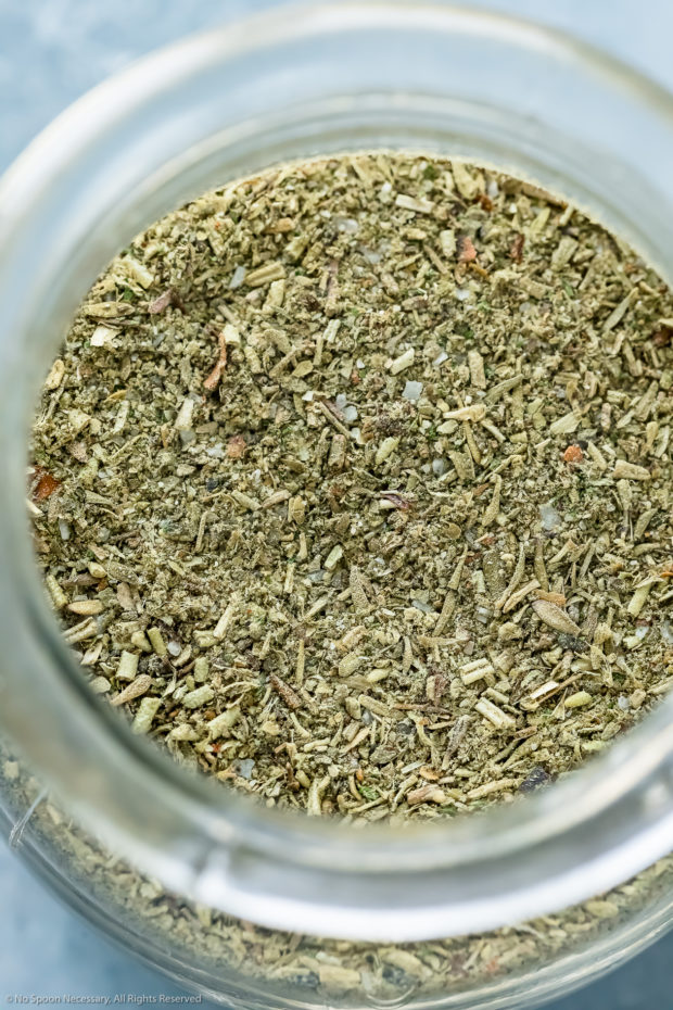 Overhead, up-close photo of Italian spice blend in a small glass jar.