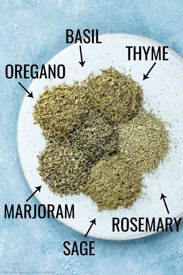 Overhead photo of the main ingredients in Italian seasoning neatly arranged on a plate with the name of each ingredient written out next to it - photo of step 1 of the recipe.