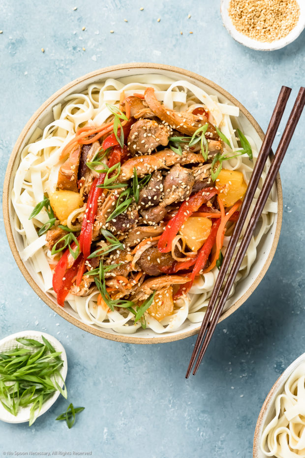 Overhead shot of Slow Cooker Sweet Chili Chicken on a bed of lo mein noodles in a neutral colored bowl with a pair of wooden chopsticks resting on the side of the bowl and ramekins of sesame seeds and sliced scallions arranged around the bowl.