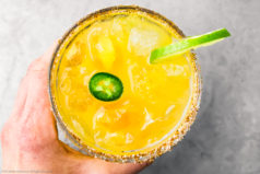 Overhead photo of a hand holding a spicy mango margarita garnished with a jalapeno slice and wheel of lime.
