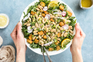 Overhead photo of two hands holding Cannellini Bean Salad a white platter with serving spoons inserted into the salad and a light tan linen, ramekin of grated parmesan and jar of lemon parmesan vinaigrette arranged around the platter.
