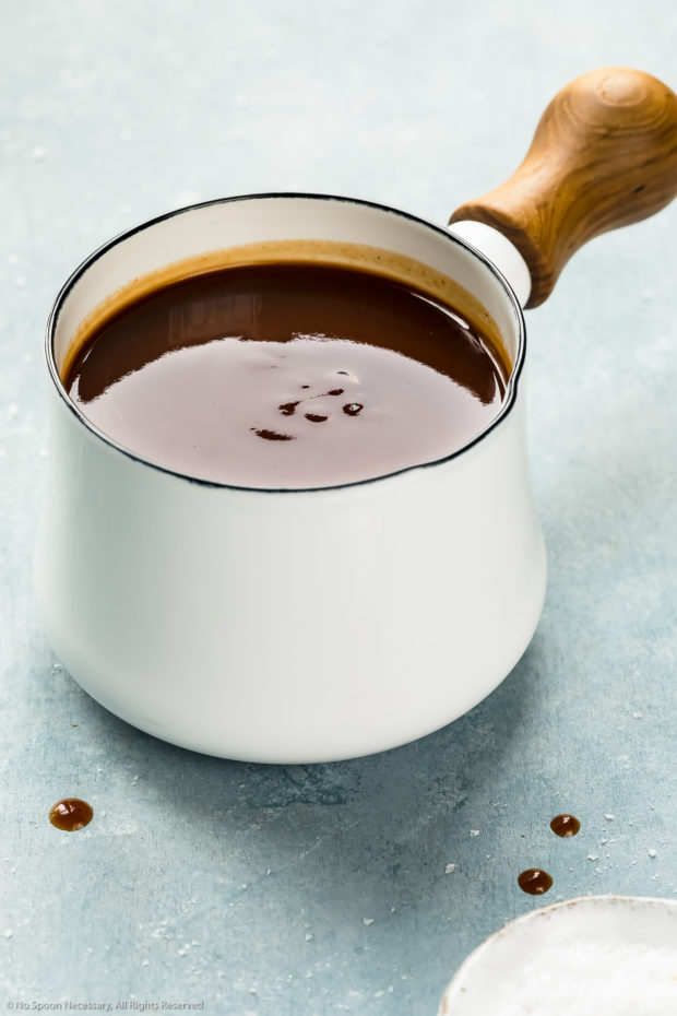 Angled photo of Carolina barbecue sauce in a small white sauce pan on a blue surface.