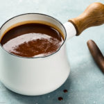 Angled photo of Carolina BBQ sauce in a small white sauce pan with a wooden spoon of sauce off to the side.