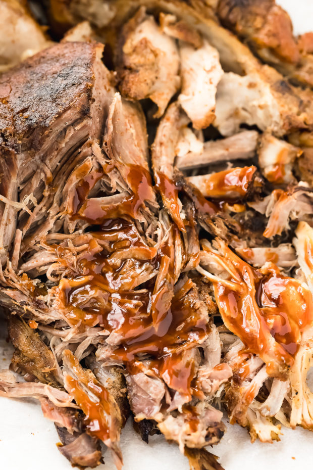 Angled, up-close photo of Carolina barbeque sauce drizzled on pulled pork.