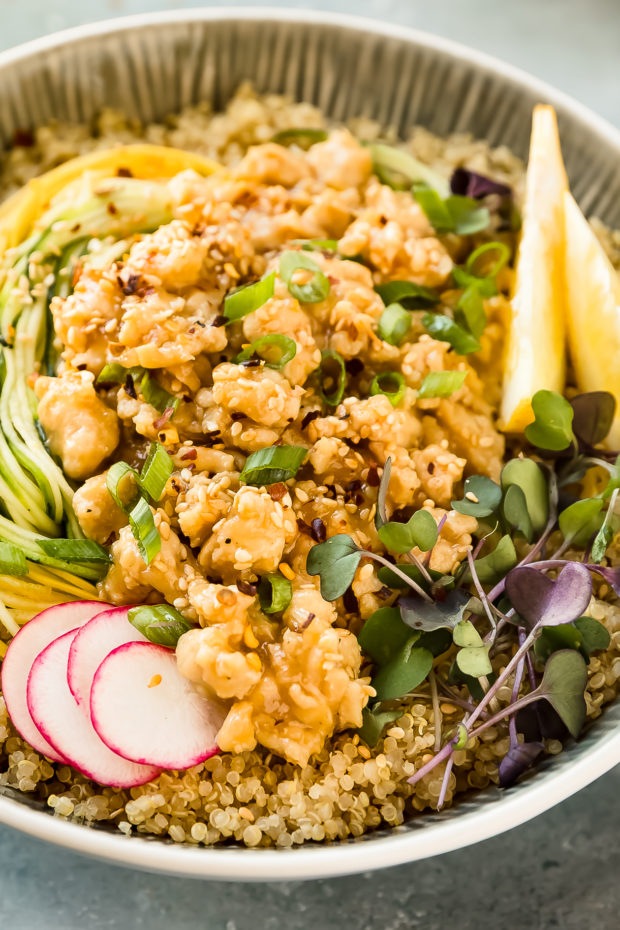Angled, close-up photo of stir-fried Lemon Chicken served over quinoa and vegetables noodles in a white bowl.