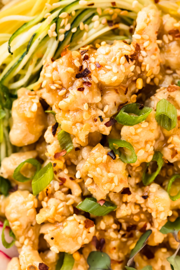 Overhead, extreme close-up photo of Honey Lemon Chicken Stir Fry garnished with sesame seeds, red pepper flakes and scallions.
