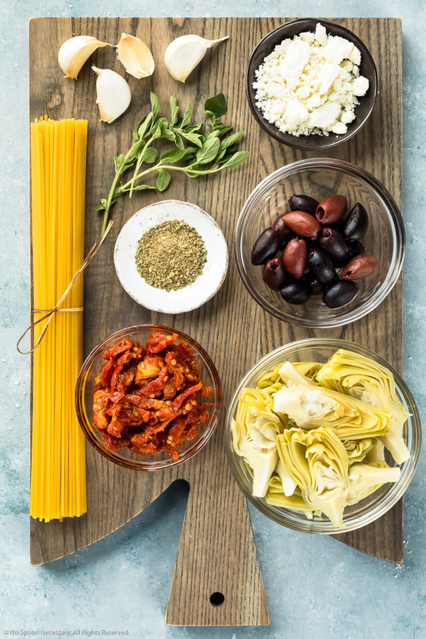 Overhead photo of all the ingredients needed to make Mediterranean Pasta Recipe with Chicken neatly organized in individual bowls on a gray wood board.