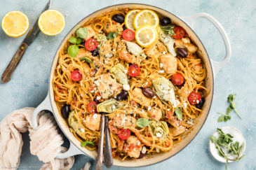 Overhead, landscape photo of Mediterranean Chicken Pasta in a large gray enamel skillet with lemon wedges, a ramekin of fresh oregano and a neutral colored linen arranged around the skillet.