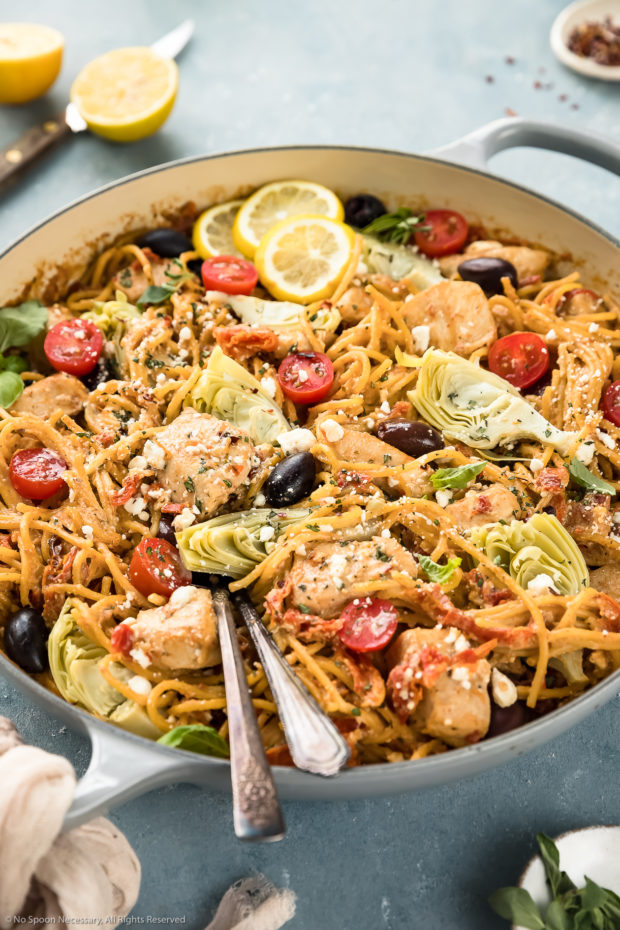 Angled photo of Mediterranean Chicken Pasta in a large gray enamel skillet with lemon wedges and ramekins of fresh oregano and crushed pepper flakes arranged around the skillet.