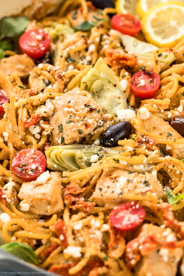 Angled, up-close photo of Mediterranean Chicken Pasta garnished with crumbled feta and crushed pepper flakes with the focus of the shot on a piece of chicken.