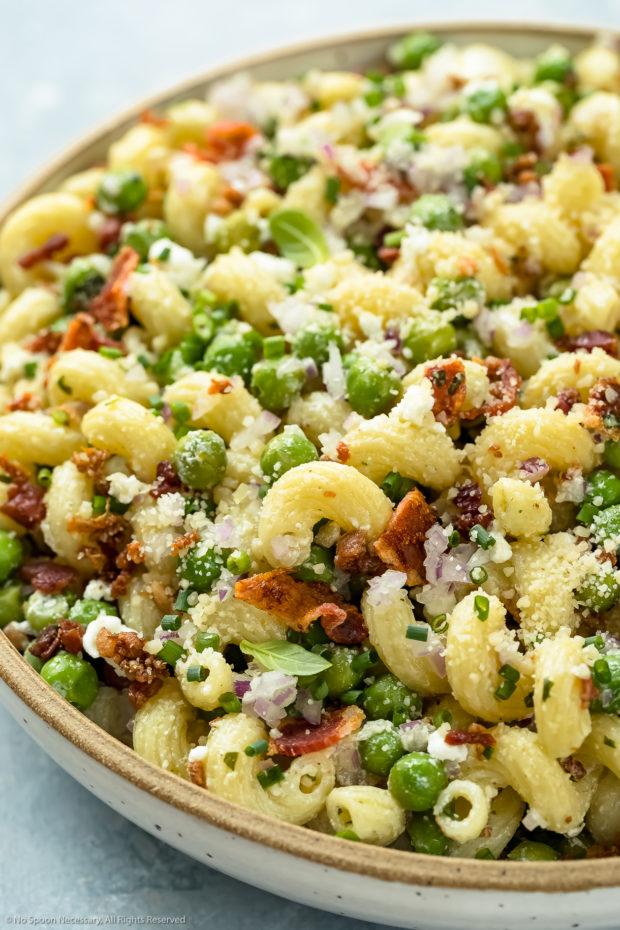Up close, angled photo of Bacon Pea Pasta Salad in a white bowl.