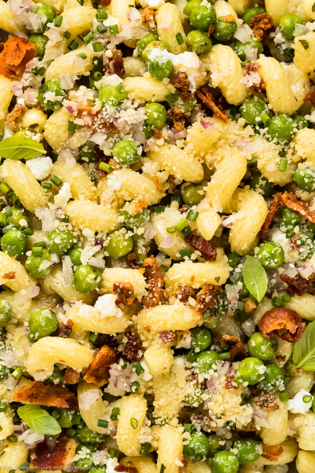 Overhead close-up photo of no-mayo pasta salad with bacon, peas, cheese, red onion and fresh herbs.