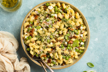 Overhead photo of Bacon Pea Pasta Salad in a white bowl with serving spoons tucked into the salad and a neutral linen, jar of basil vinaigrette and ramekin of fresh basil arranged around the bowl.