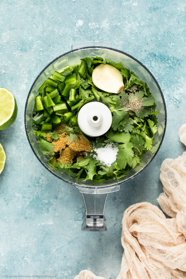 Overhead photo of all the ingredients needed to make honey cilantro vinaigrette in the bowl of a food processor with lime wedges and a neutral colored linen arranged around the bowl - photo of step 1 of the cucumber avocado salad recipe.