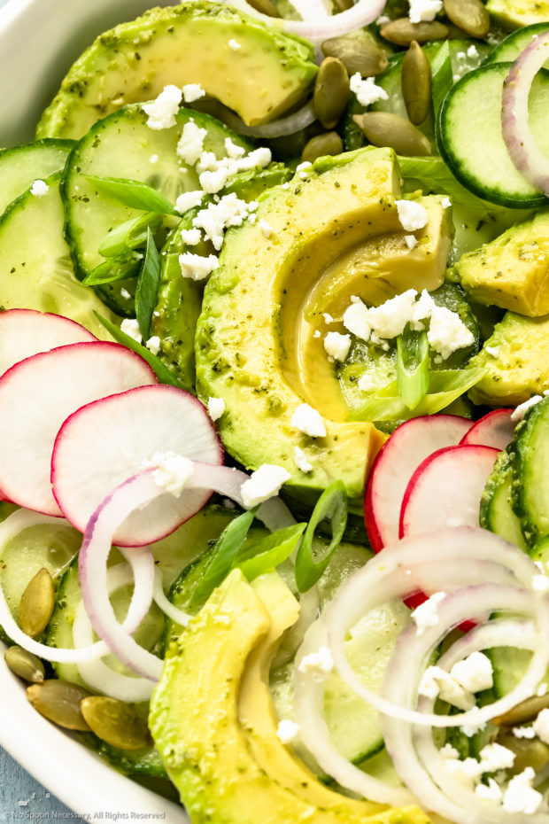 Angled, up-close photo of Cucumber Avocado Salad garnished with cilantro, queso fresco and radishes in a white bowl.
