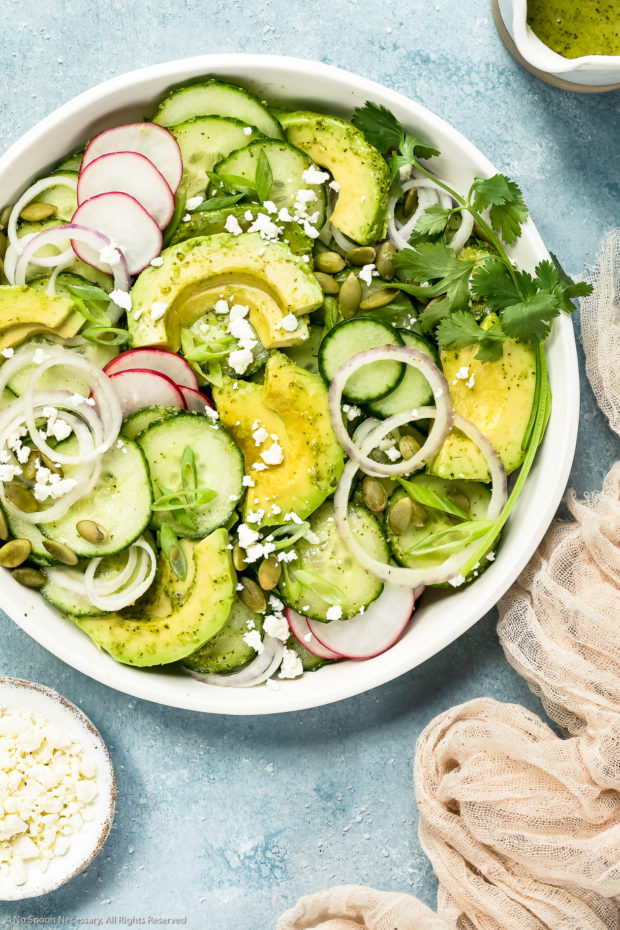 Overhead photo of Cucumber Avocado Salad garnished with cilantro, queso fresco and radishes in a white bowl with a jar of cilantro vinaigrette, ramekin of cheese and neutral colored linen arranged around the bowl.