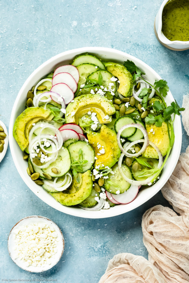 Overhead photo of Cucumber Avocado Salad garnished with cilantro, queso fresco and radishes in a white bowl with a jar of cilantro vinaigrette and ramekins of cheese and pepitas arranged around the bowl.