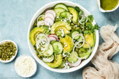 Overhead, landscape photo of Cucumber Avocado Salad garnished with cilantro, queso fresco and radishes in a white bowl with a jar of cilantro vinaigrette and ramekins of cheese and pepitas arranged around the bowl.